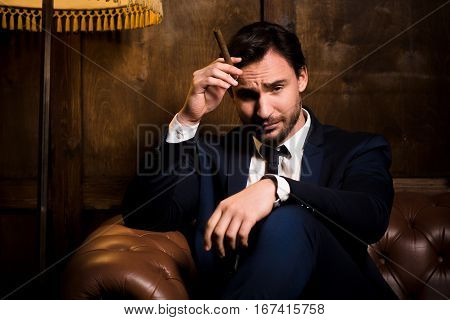 Veteran stockbroker sitting on sofa and smoking cigar. Handsome businessman in navy blue business suit looking at camera. Wealth, business concept.