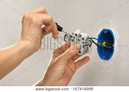 hands of electrician installing electrical socket with screwdriver
