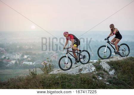 Couple Bicyclist With Mountain Bikes On The Hill At Sunset