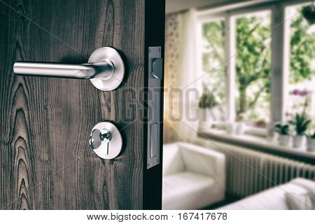 Brown door with metal doorknob and lock against sofas by cabinets at home