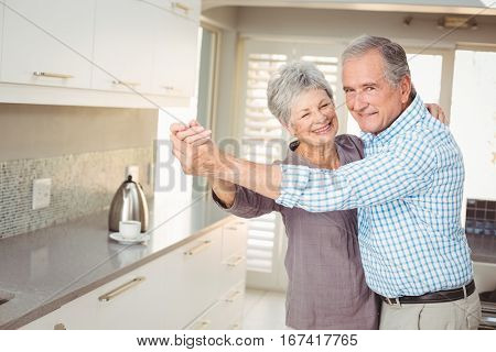 Portrait of cheerful senior man dancing with wife in kitchen