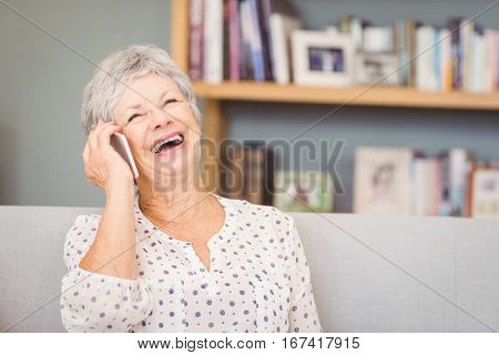 Senior woman talking on mobile phone at home