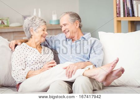 Happy senior couple sitting on sofa in living room at home