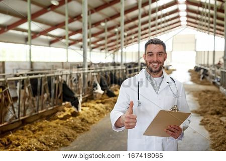 agriculture industry, farming, people and animal husbandry concept - veterinarian or doctor with clipboard and herd of cows in cowshed on dairy farm showing thumbs up hand sign
