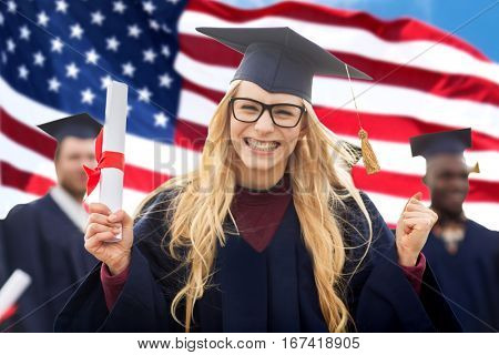 education, gesture and people concept - group of happy international students in mortarboards and bachelor gowns with diplomas celebrating successful graduation over american flag background