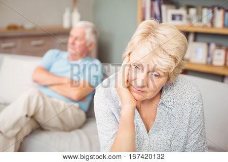 Tensed senior couple sitting on sofa at home