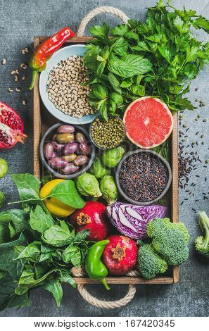 Fresh vegetables and fruits, seeds, cereals, beans, spices, superfoods, herbs, condiment in wooden box for vegan, allergy-friendly, clean eating and raw diet. Grey concrete background and top view