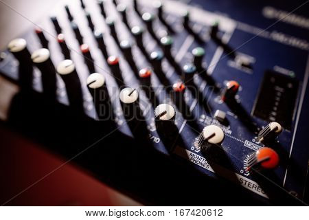 Close up shot of a mixer desk with many buttons.