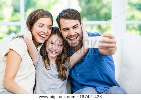 Laughing family clicking selfie with smartphone at home