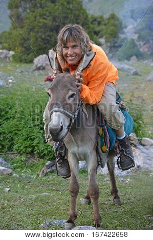 Smiling woman dressed in orange anorak is sitting on donkey. She keeps donkey's ears in her hands. Travel scene.