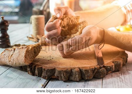 Hands breaking bread. Baguette piece on wooden board. Finest baked products.