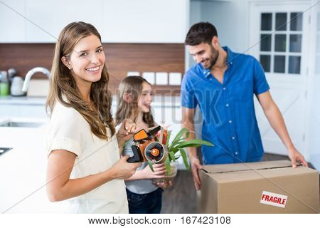 Portrait of woman helping family in packing at home