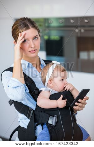 Tensed woman with mobile phone carrying baby girl at home