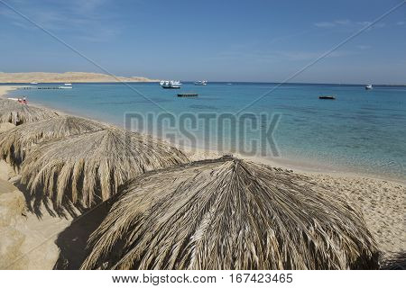Top view of sand beach with sunshades. Blue sea sky and ships in background.