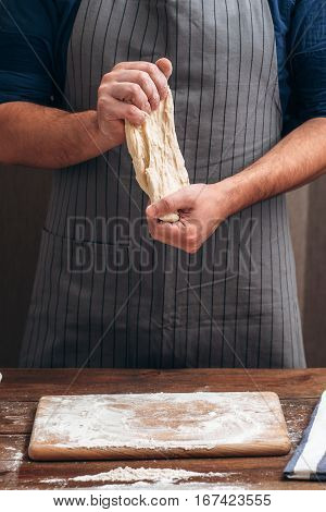 Unrecognizable baker stretching dough at kitchen. Man kneading raw pastry before forming, bakery professional preparing. Homemade bakery, kitchen, cooking process concept
