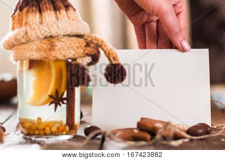 Blank card with hot punch closeup. Female hand holding blank card near glass jar with warm winter drink of orange, cinnamon and anise, decorated with knitted cover, free space