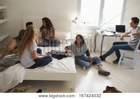 Five teenage friends hanging out together in bedroom