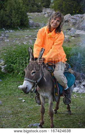 Smiling woman dressed in orange anorak is sitting on donkey. Travel scene.