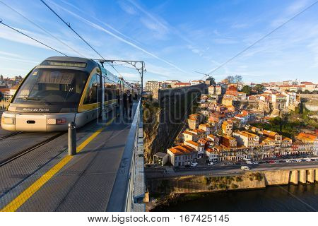 PORTO, PORTUGAL - JAN 11, 2017: Train of Porto Metro on Dom Luis iron Bridge in Old Town. The network has 6 lines and reaches seven municipalities within the metropolitan Porto area.