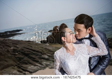 Asian Couple Wearing Wedding Dress And Suit For Beach Wedding Ceremony. Couple On The Beach Concept.