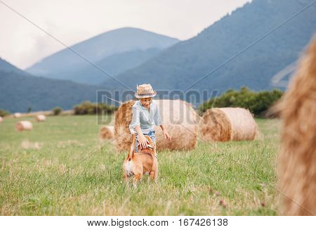 Boy plays with dog on the field with hayroll