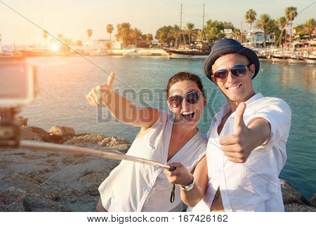 Positive young couple take a selfie photo in tropical harbor