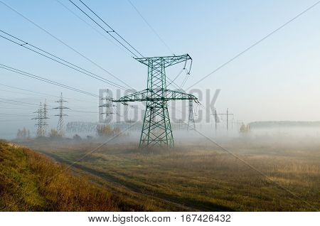 Electricity transmission line in morning mist. Electric constructions stand on grassland.