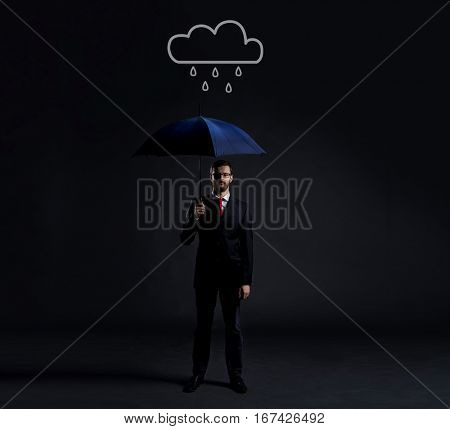 Businessman with umbrella standing under the rain. Dark, dramatic background. Business, failure, crisis, concept.