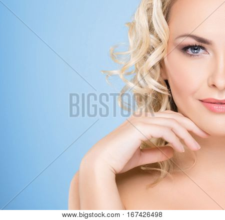Half face portrait of young and beautiful woman with curly blond hair over background.