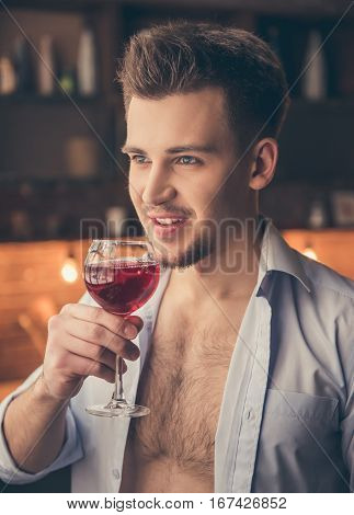 Sexy guy in unbuttoned shirt is drinking wine and smiling while standing in the kitchen