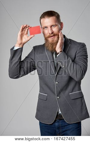 Surprised hipster business man with beard and mustashes in suit standing over grey background showing blank credit card looking at camera in amazement with hand on cheek.