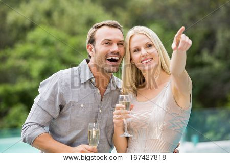 Smiling woman pointing while standing by man holding champagne flute at poolside