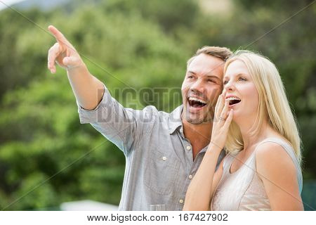 Smiling man pointing while standing by surprised woman at resort