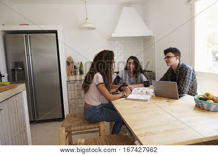 Three teens talk as they study in a kitchen using a computer