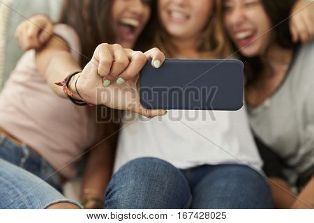 Three teenage girls taking selfie at home, focus on phone