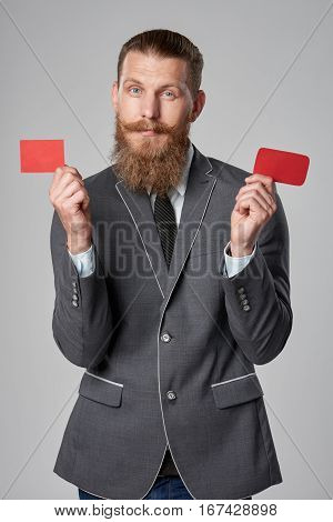 Hipster business man with beard and mustashes in suit standing over grey background showing two blank credit cards in every hand