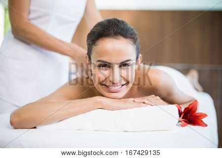 Close-up portrait of young woman smiling while receiving massage at health spa