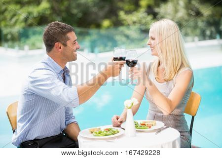 Smiling couple holding red wine while sitting at poolside