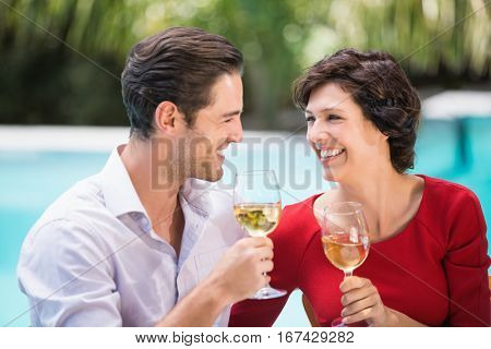Happy couple holding white wine while sitting at poolside