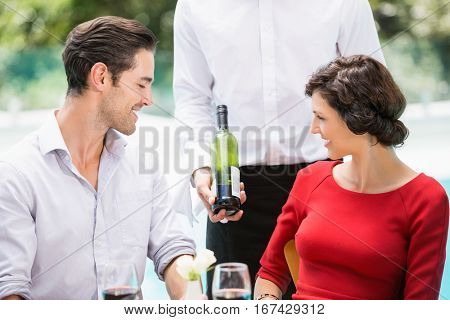 Midsection of waiter showing wine bottle to couple at poolside