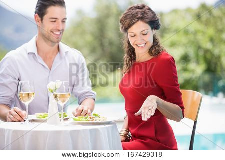 Smiling woman looking at engagement ring while sitting at poolside