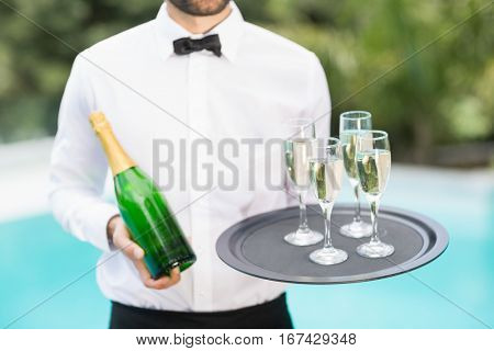 Midsection of waiter holding champagne flutes and bottle at poolside