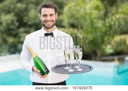 Portrait of smiling waiter holding champagne flutes and bottle at poolside