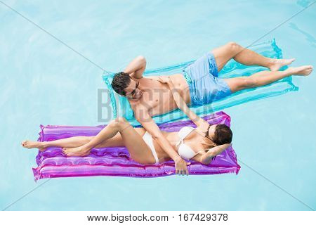 High angle view of couple enjoying on inflatable raft at swimming pool