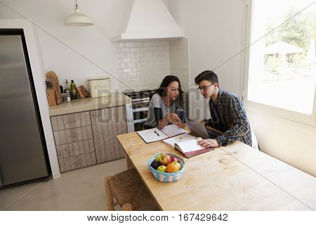 Teenagers study with laptop and phone in kitchen, elevated view