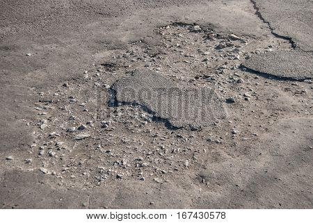 grey road with potholes - close up