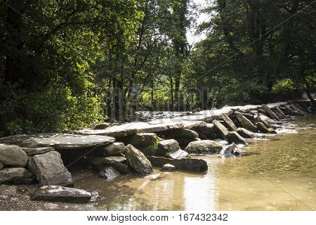 Clapper bridge over river in sunshine at Tarr Steps on Exmoor in Somerset