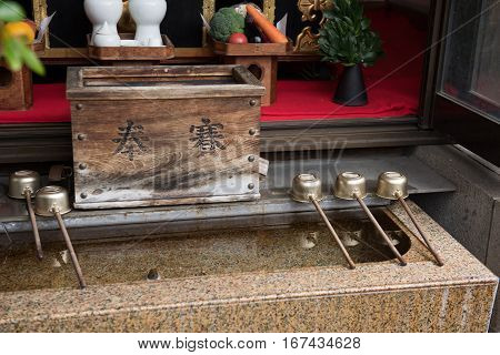 In the picture we can see a photo of a monastery where holy water is stored and some wooden handle spoons are kept on the top of the water reservoir.