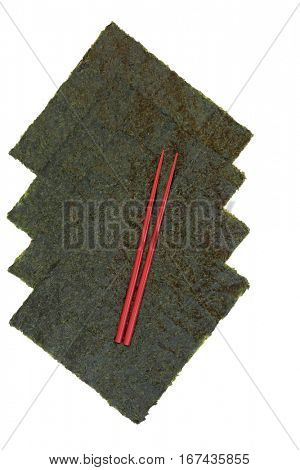Nori japanese seaweed with red chopsticks on white background with copy space.