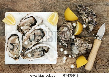 Oysters on ice with pearls on a square plate with oyster knife and  lemon fruit on old wooden background.